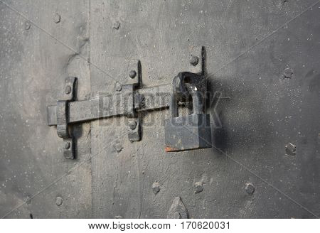 Old big padlock. Closed metal door with old lock.