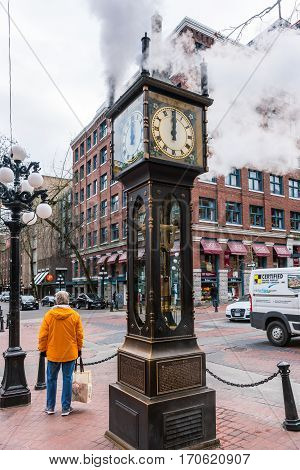 Vancouver Canada - January 28 2017: The historic steam clock strikes midday in Gastown downtown Vancouver with jets of steam rising from the clock.