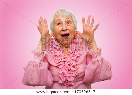 Elderly surprised woman screaming on rose studio background
