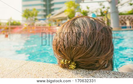 Asian girl head relaxing resting on poolside