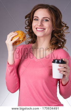 young beautiful girl with a sandwich and a cup of coffee from a fast food smiling on a gray background
