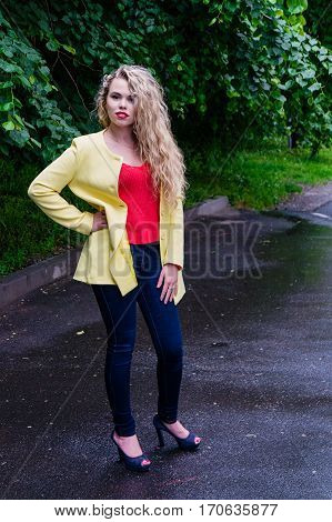 Charming blonde girl student posing for the camera in a green park is wearing a yellow jacket, red jacket, jeans and slippers for heels