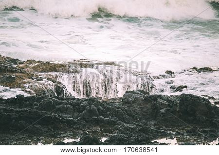 Waves crashing on the shore at sunset. Thor's Well Cape Perpetua Oregon USA.