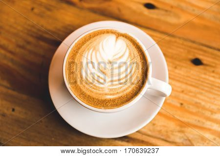 A carefully prepared cappuccino in a simple white cup and plate sitting on wooden table.