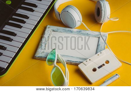 Audio Cassette And Headphones On A Yellow Background. Music Concept
