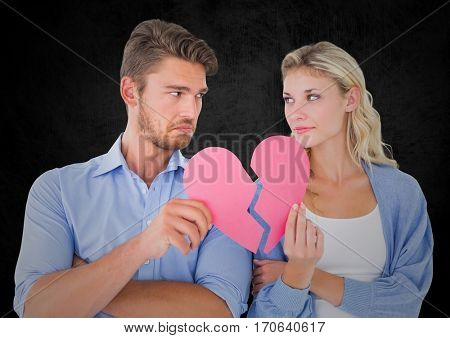 Depressed couple holding broken heart and looking at each other