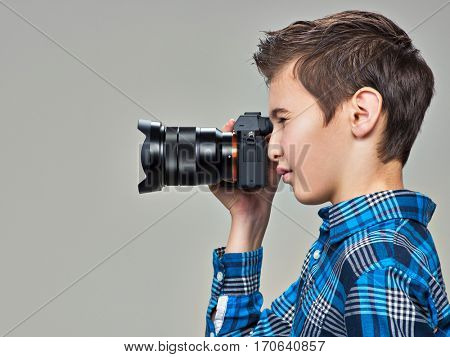 Boy with photo camera taking pictures. Teen boy  with photo camera photographing. Profile portrait