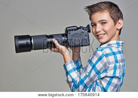 Boy holds big photo camera with telephoto lenses
