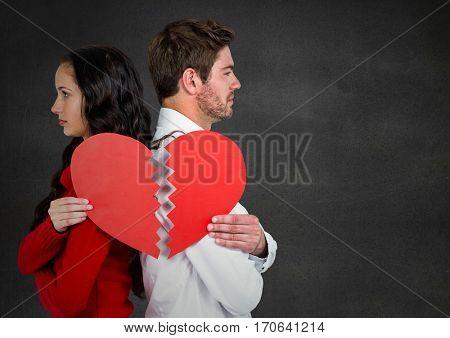 Depressed couple standing back to back holding broken heart