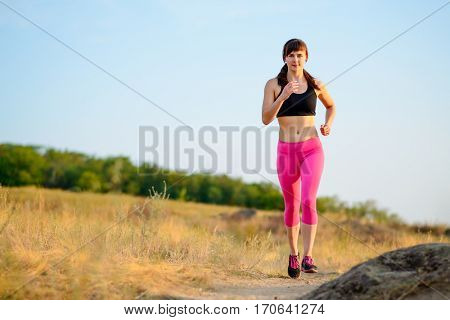 Young Woman Running on the Trail in the Morning. Active Lifestyle Concept.