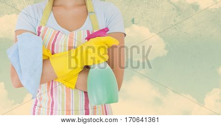 Mid section of woman in apron holding spray bottle against sky background