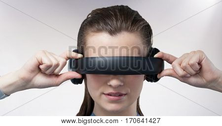 Close-up of woman using virtual reality headset against white background