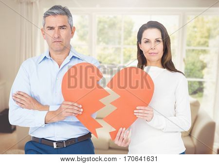 Digital image of couple holding a broken heart in a living room