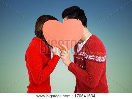 Romantic couple holding heart shape and kissing each other against blue background