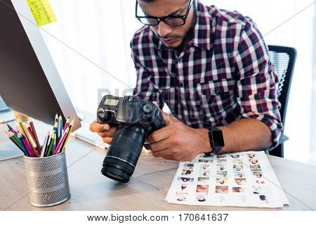 Side view of photographer working at desk in office