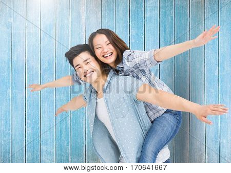 Portrait of happy man giving woman piggyback against wooden background