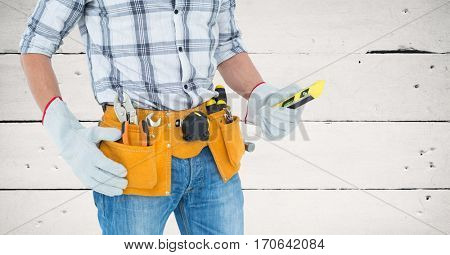 Mid section of handy mans torso with tool belt against wooden panel