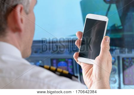 Airline pilot wearing uniform with epauletes using smart phone in airplane cockpit