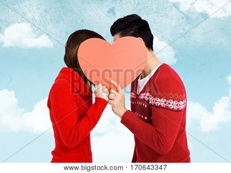 Romantic couple holding heart shape and kissing each other against sky