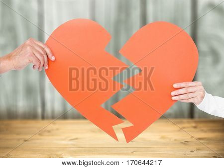 Close-up of couple hands holding a broken heart