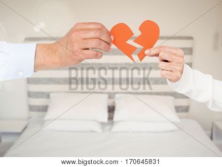 Hands of couple holding a broken heart in bedroom at home