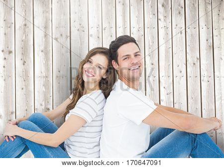 Happy couple sitting back to back against wooden background