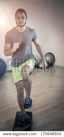Portrait of serious man doing exercise on aerobic stepper in fitness studio