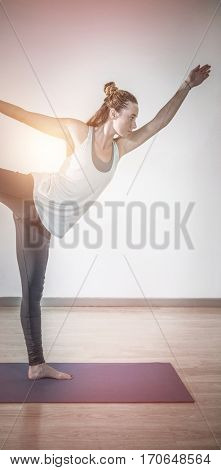 Woman in lord of dance yoga pose in fitness studio