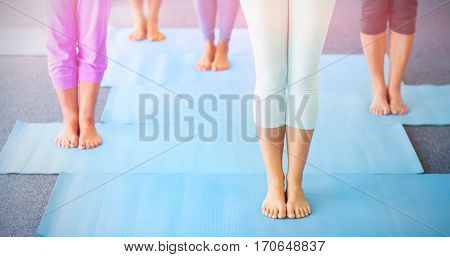 Low section of instructor performing yoga with seniors during sports class