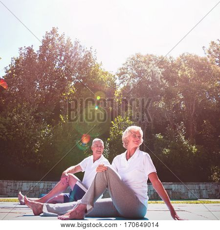 Senior couple exercising at poolside against sky during sunny day