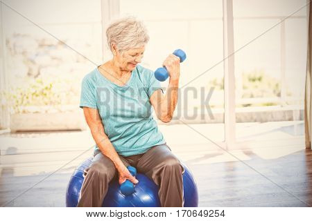 Smiling senior woman holding dumbbell while sitting on exercise ball at home