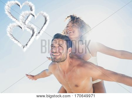 Composite image of man giving piggy back to woman on beach against heart in background