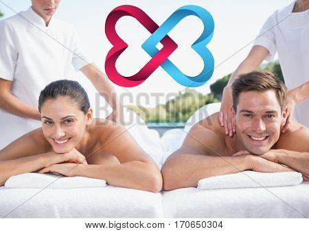 Couple receiving massage in spa and and digitally generated interlocked hearts