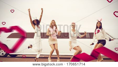 Happy female friends jumping in front of limousine against hearts
