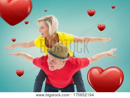 Senior man giving piggy back to woman with digitally generated hearts