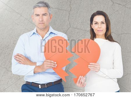 Upset couple holding broken heart against digitally generated wall background