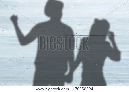 Cheerful man gesturing while holding woman hand against bleached wooden planks background