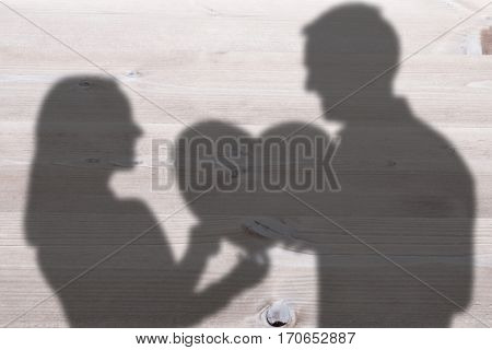 Smiling couple holding heart shape paper against bleached wooden planks background