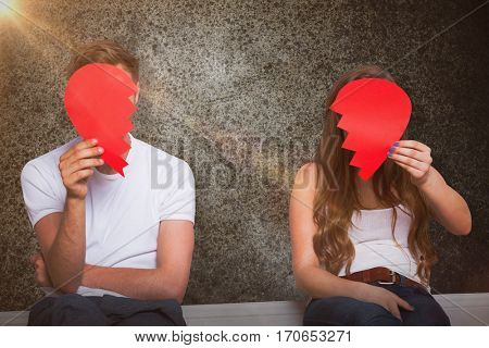 Couple holding broken heart against close-up of road surface