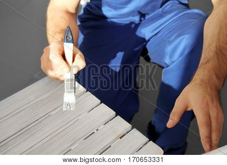Close up view of decorator painting furniture