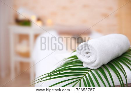 Rolled up white spa towel on blurred background