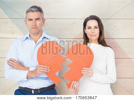 Portrait of sad mature couple holding broken hearts against wooden background