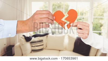 Hand of couple holding broken hearts at home