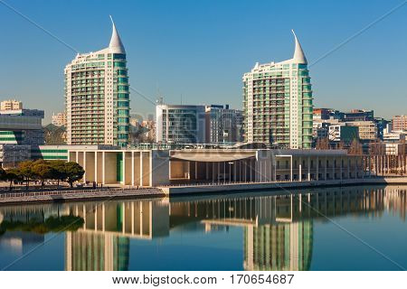 Modern tall residential buildings reflecting in the water under blue sky in Lisbon, Portugal.