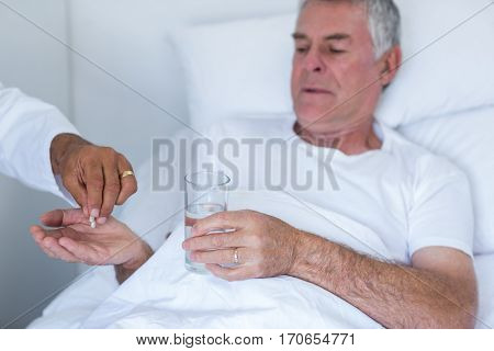 Male doctor giving pill to senior man in hospital