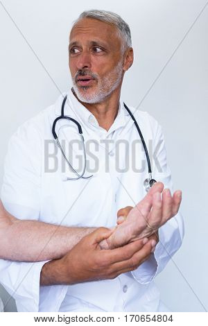 Male doctor giving palm acupressure treatment to the patient in the hospital