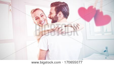 Hearts hanging on a line against woman holding pregnancy test while embracing man