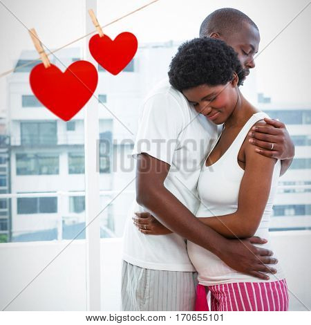 Hearts hanging on a line against pregnant couple cuddling at home