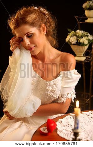 Bride in wedding dress holding veil. Girl undresses for night. Candle illuminates room. Jewelry rings and dreams about choice of groom. Baskets of flowers on a black background.
