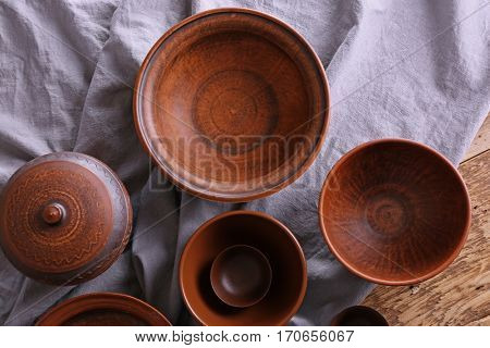 Set of dishes with tablecloth on wooden table